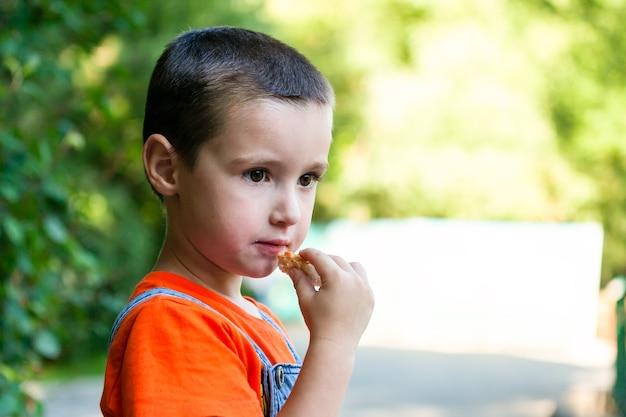 Um garotinho fofo que come um pedaço de pão e desvia o olhar em um parque verde da cidade em um dia quente de verão