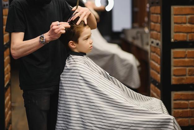 Um garotinho fofo senta em um cabeleireiro no estilista, um estudante está cortando o cabelo em um salão de beleza, uma criança em uma barbearia, um corte de cabelo curto de homem.