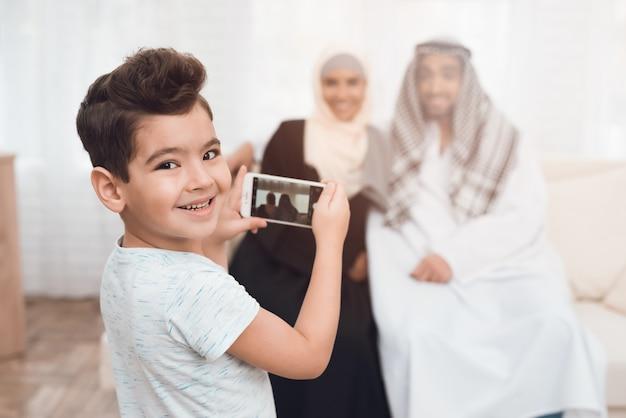 Um garotinho fotografando sua mãe e seu pai.