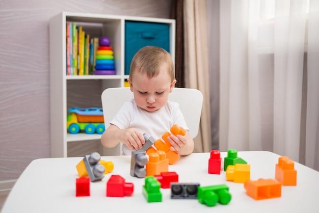 Um garotinho joga uma construção multicolorida colocada em uma mesa no quarto das crianças