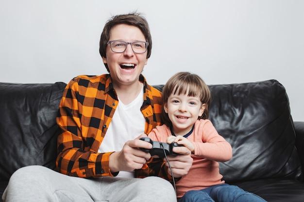 Um garotinho jogando videogame com o pai.