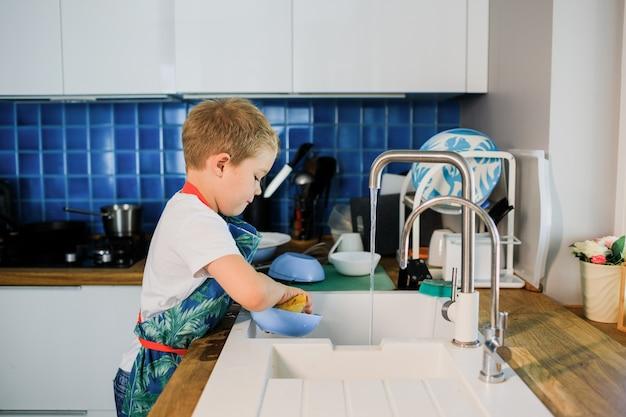 Um garotinho lava a louça em uma cozinha moderna.
