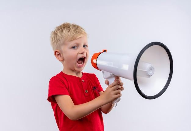 Um garotinho loiro fofo com uma camiseta vermelha falando no megafone enquanto olha para uma parede branca
