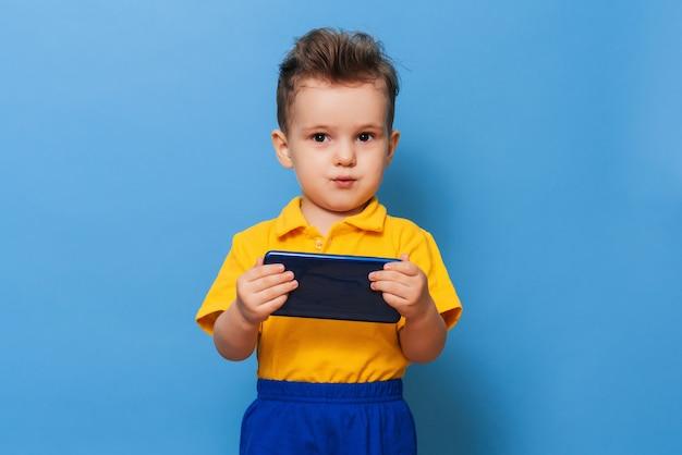 Um garotinho olha para a tela de um telefone celular. foto em uma parede azul.