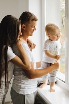 Um garotinho olha pela janela e seus pais o admiram