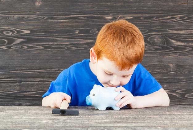 Um garotinho ruivo estudando o conteúdo de seu cofrinho azul, encontra um martelo que esmagaria um cofrinho de porco