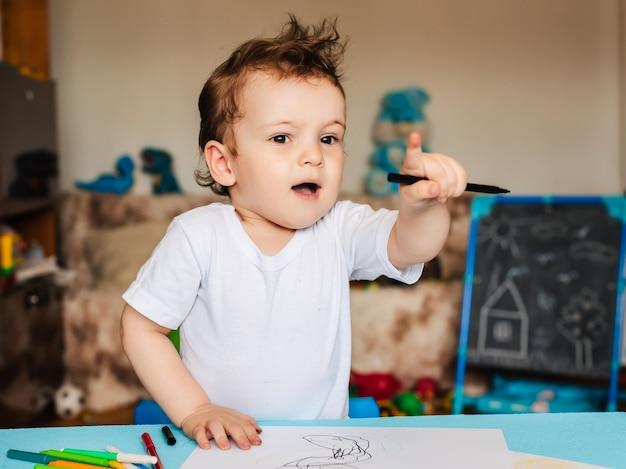 Um garotinho se senta em uma cadeira e desenha com lápis de cor