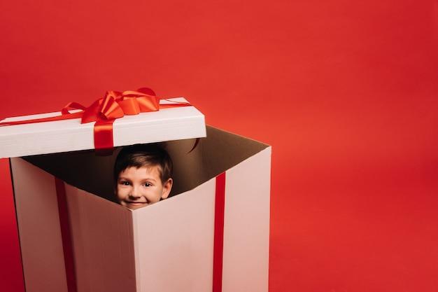 Um garotinho sentado em um presente de natal e olhando para fora dele sobre um fundo vermelho