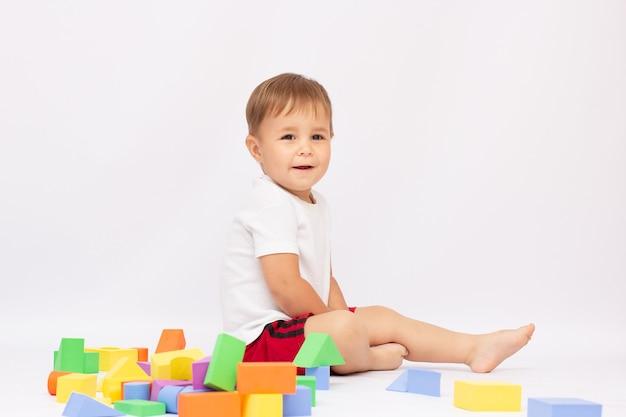 Um garotinho sentado no chão brincando com cubos sorrindo, isolado em um fundo branco.
