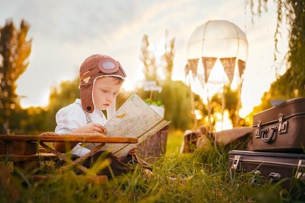 Um garotinho sonha em se tornar um piloto olhando um mapa ao ar livre