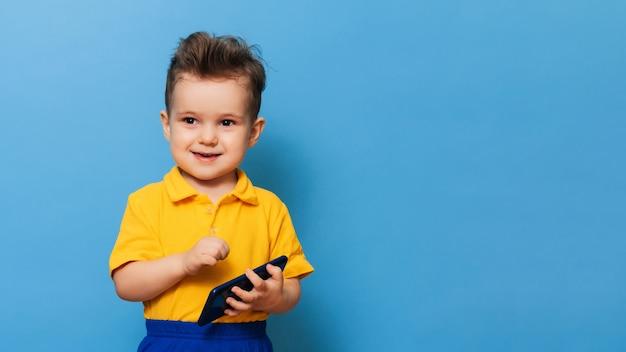 Um garotinho tem um celular nas mãos.