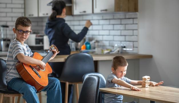 Um garotinho toca violão, e seu irmão constrói uma torre com cubos de madeira em casa na mesa.