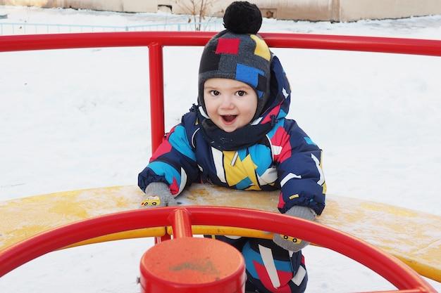 Um garoto alegre de 2 anos de chapéu e macacão gira no inverno em um carrossel de rua. alegre e alegre.