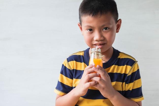 Um garoto asiático está bebendo uma garrafa de suco de laranja.