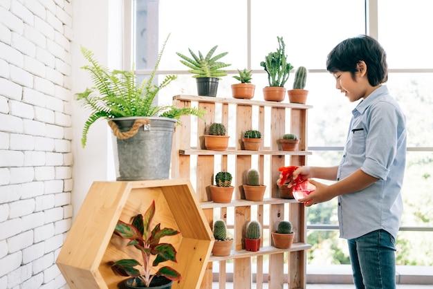 Um garoto asiático gosta de cuidar das plantas regando com um spray de água em uma planta de casa em casa.