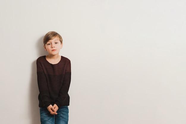 Um garoto bonito com rosto infeliz, inclina-se para uma parede branca