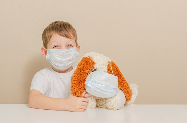 Um garoto bonito de 4 anos e seu cachorro de pelúcia com uma máscara médica estão sentados em casa em quarentena. auto-isolamento.