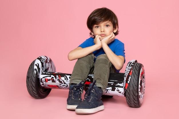Um garoto bonito de vista frontal em camiseta azul e calça cáqui andando segway no espaço rosa