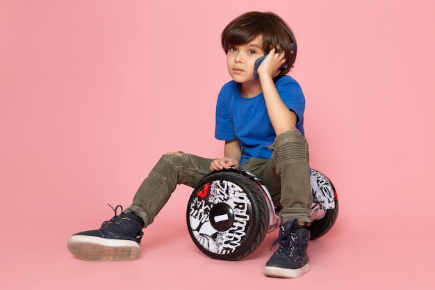Um garoto bonito de vista frontal em camiseta azul e calça cáqui, falando ao telefone andando de segway no chão rosa