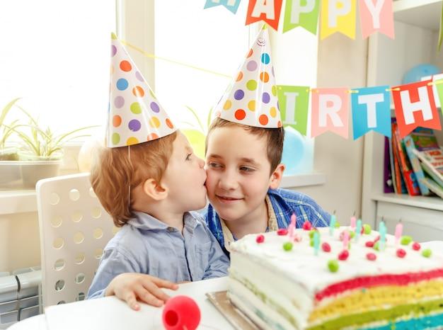 Um garoto bonito deseja feliz aniversário a seu irmão. relações familiares