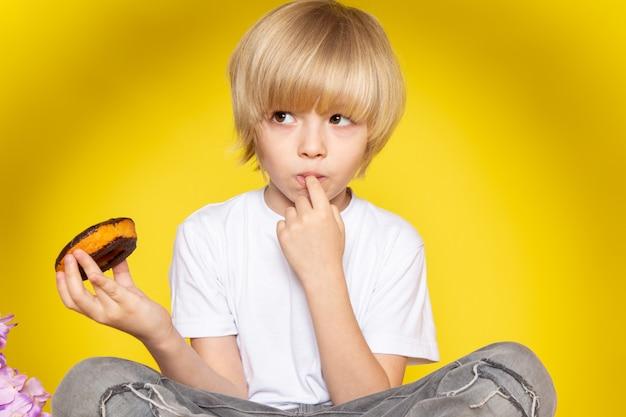 Um garoto bonito loiro vista frontal em camiseta branca comendo rosquinhas no espaço amarelo