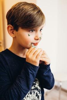 Um garoto bonito pinta o rosto com creme de cor comestível