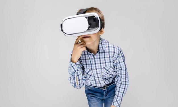 Um garoto charmoso com uma camisa embutida e jeans claro fica em um cinza. o menino em seu rosto óculos de realidade virtual