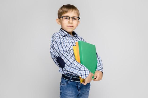 Um garoto charmoso com uma camisa vkletchatoy e calça jeans clara fica em um cinza. o menino tem nas mãos uma pasta multicolorida com documentos