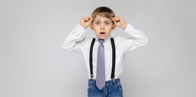 Um garoto charmoso de camisa branca, suspensórios, gravata e jeans claro fica em um cinza. o garoto segura seus óculos