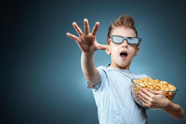 Um garoto com pipoca nas mãos assistindo a um filme em 3d óculos, medo, parede azul. o conceito de cinema, filmes, emoções, surpresa, lazer. plataformas de streaming.