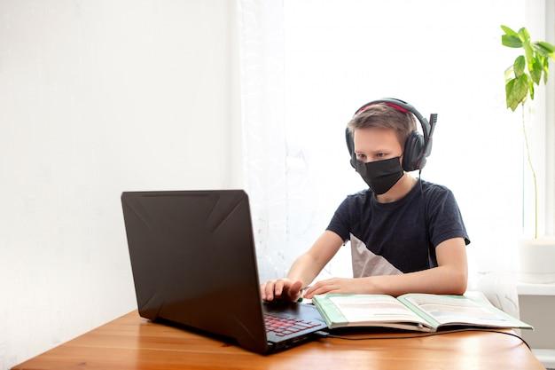Um garoto com uma máscara descartável e fones de ouvido em casa na frente de um computador faz a lição de casa.