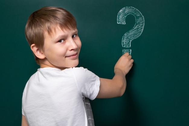 Um garoto de aparência caucasiana escreve um ponto de interrogação no quadro-negro. sorrir. solução fácil para o problema.