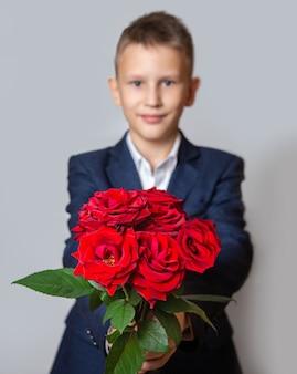 Um garoto de terno azul segura um buquê de rosas vermelhas. cinzento .
