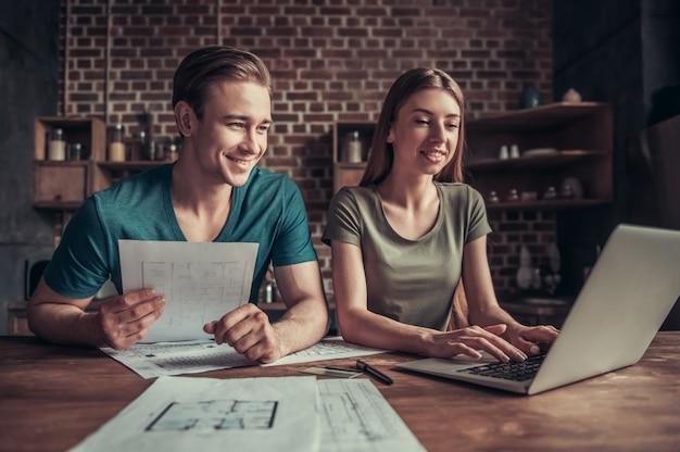 Um garoto e uma garota olham para um notebook enquanto está sentado em uma mesa de trabalho. dois funcionários sentam-se no escritório e trabalham.