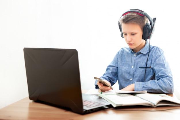 Um garoto em fones de ouvido na frente de um computador faz a lição de casa.