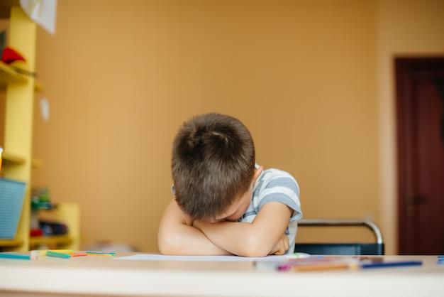 Um garoto em idade escolar faz a lição de casa em casa. treinamento na escola