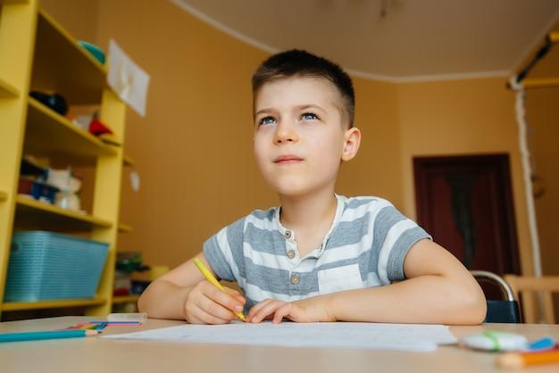 Um garoto em idade escolar faz a lição de casa em casa.