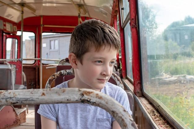 Um garoto em um velho ônibus vintage, ele está triste porque sua vida pobre e o ônibus se movendo por uma estrada suja
