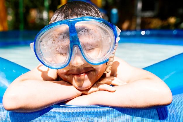 Um garoto em uma máscara de água perto da piscina com os olhos fechados