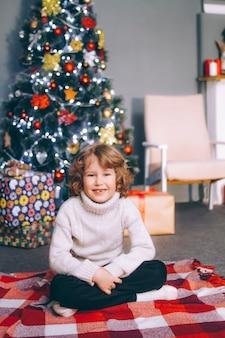 Um garoto encaracolado de dez anos sem dentes da frente senta-se ao lado da árvore do ano novo com presentes em um suéter, olha para a moldura e sorri.
