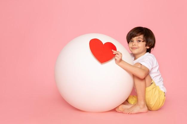 Um garoto engraçado bonito vista frontal em camiseta branca segurando coração forma brincando com bola branca redonda no chão rosa