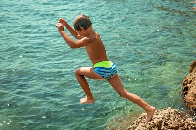 Um garoto está pulando do penhasco no mar em um dia quente de verão. férias na praia. o conceito de turismo e recreação ativos