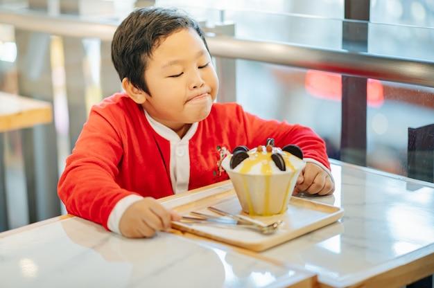 Um garoto fantasiado de papai noel e seu sorvete oreo. ele sorriu e ficou feliz.