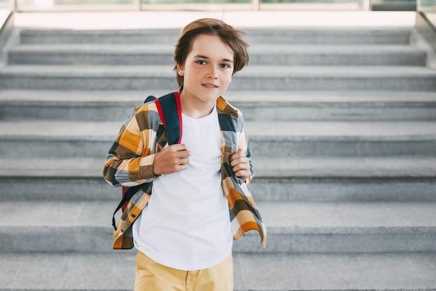 Um garoto feliz com uma mochila fica nos degraus em frente à entrada da escola e sorri lindamente