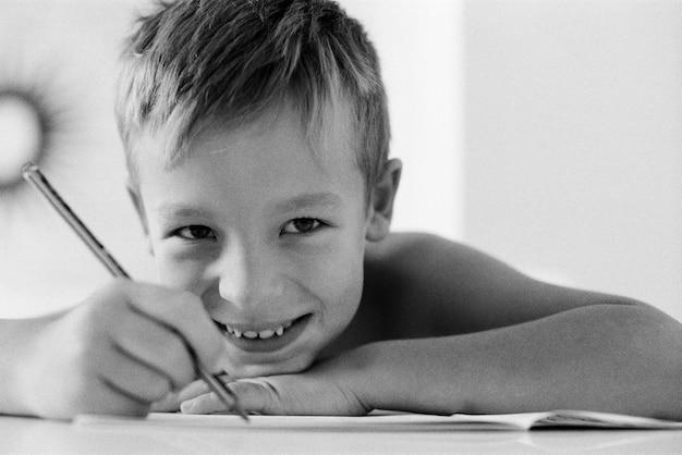 Um garoto feliz e sorridente fazendo a lição de casa