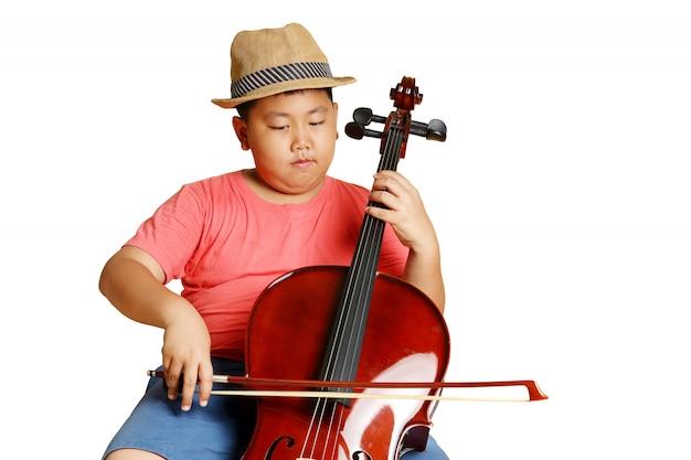 Um garoto gordo asiático de chapéu, vestindo uma camisa rosa tocando violoncelo. isolado