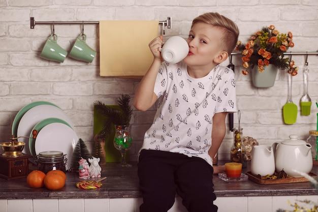 Um garoto loiro bonito está sentado na mesa da cozinha com um copo grande e branco na mão. foto engraçada