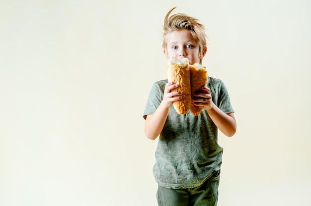 Um garoto loiro come uma baguete perfumada, bolos frescos. café da manhã saboroso