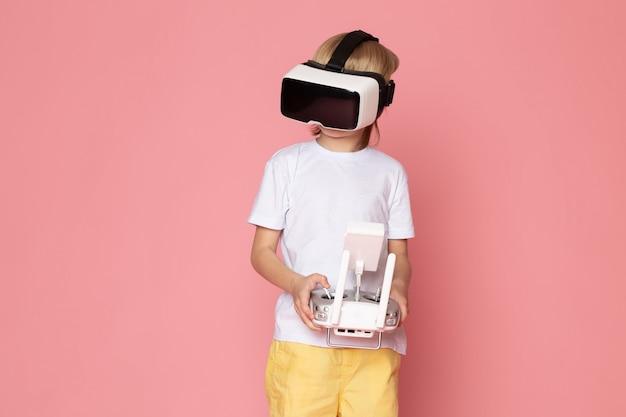 Um garoto loiro vista frontal jogando vr em camiseta branca no espaço rosa