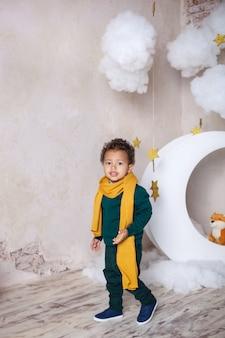 Um garoto negro fica perto do mês, luna, entre estrelas. uma criança em jogo, em fantasia. aventuras do pequeno príncipe. menino afro-americano. infância. criança brinca no jardim de infância. educação pré-escolar infantil.